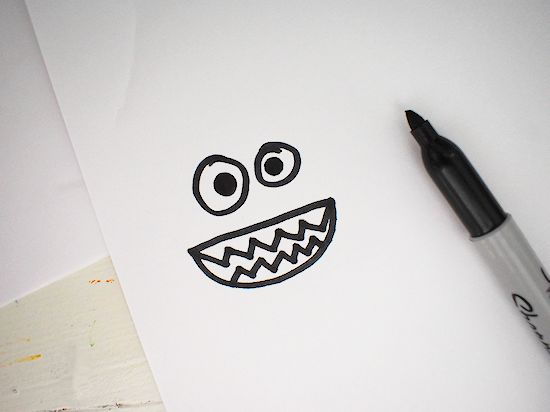 monster eyes and mouth drawn on white paper
