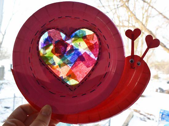 Paper Plate Snail Heart Suncatcher Craft in a window with sun shining through.