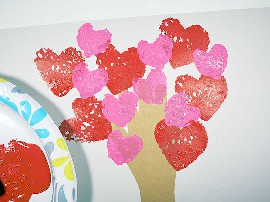 Pink heart sponge stamps around handprint tree.