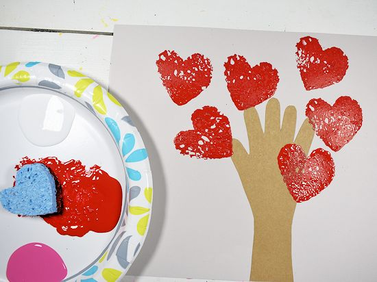 Red heart sponge stamps around handprint tree.