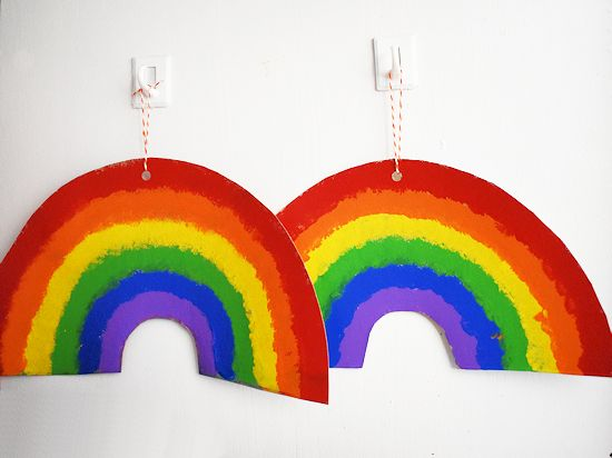 Cardboard Pom Painted Rainbows hanging by twine.