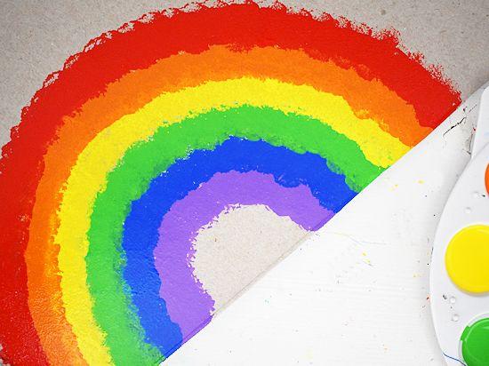 Pom painted rainbow on cereal box cardboard.