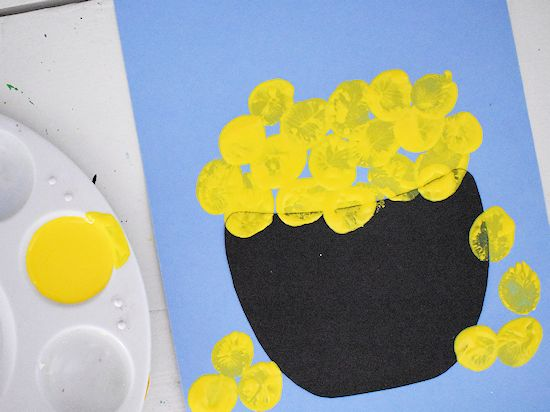 Thumbprint gold coins overflowing from pot.