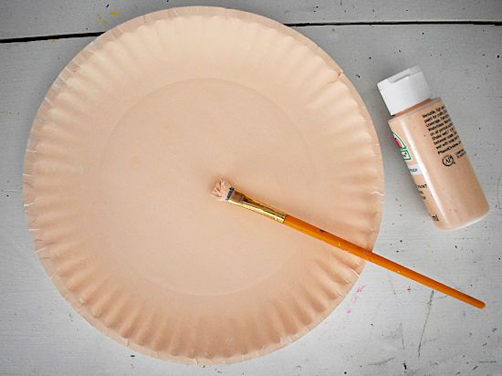 Paint a paper plate in a pale skin-toned color.