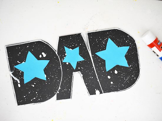 Glue the large stars in the center of the Ds and the smaller star in the A.